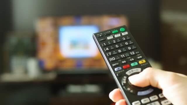 テレビのリモコンを操作している人